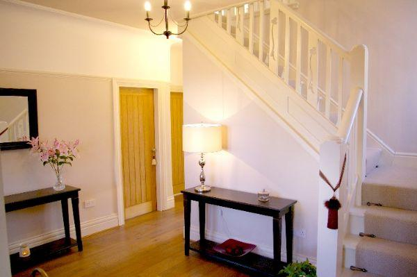 The welcoming hallway has an original staircase and lead light window
