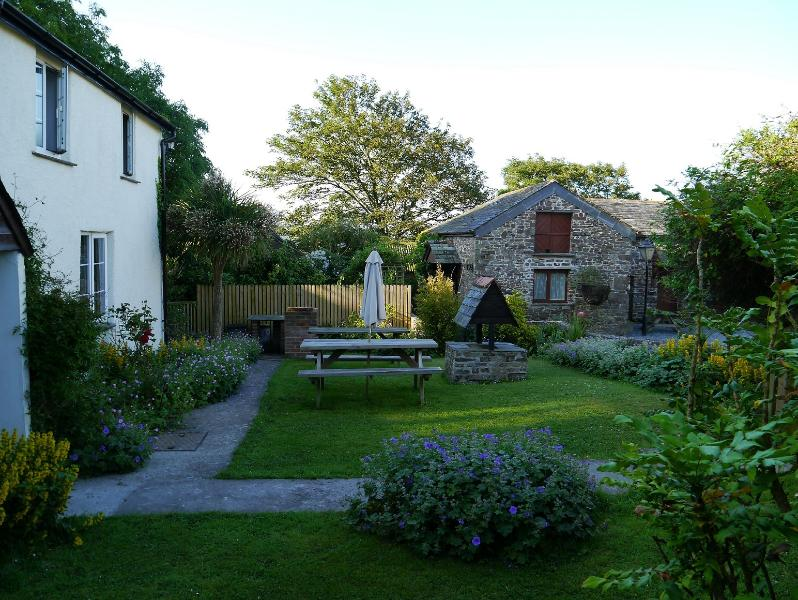 The 16th century farmhouse and private garden, with Pear Tree cottage in the background.