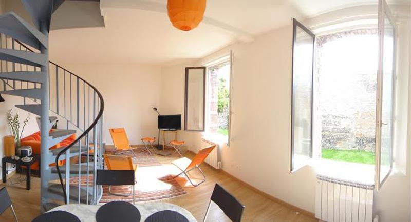 Le salon et la cuisine (équipée)  donnent sur le jardin. Couleurs noir et orange.