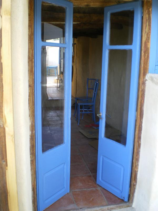 Mediterranean blue french doors lead from the terrace to the living room