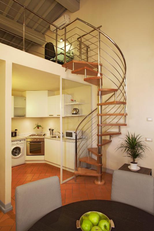 La cocina y la mesa del comedor con las escaleras para llegar a la entreplanta