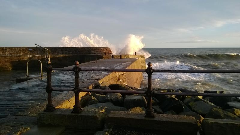 Waves breaking over harbour wall