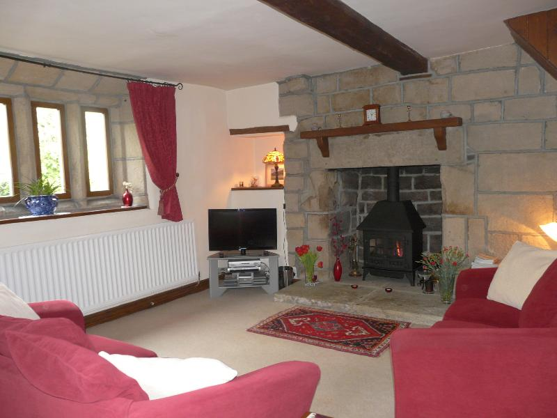 Large comfortable lounge with original mullioned windows, oak beams and stone fireplace, HD TV, DVD.