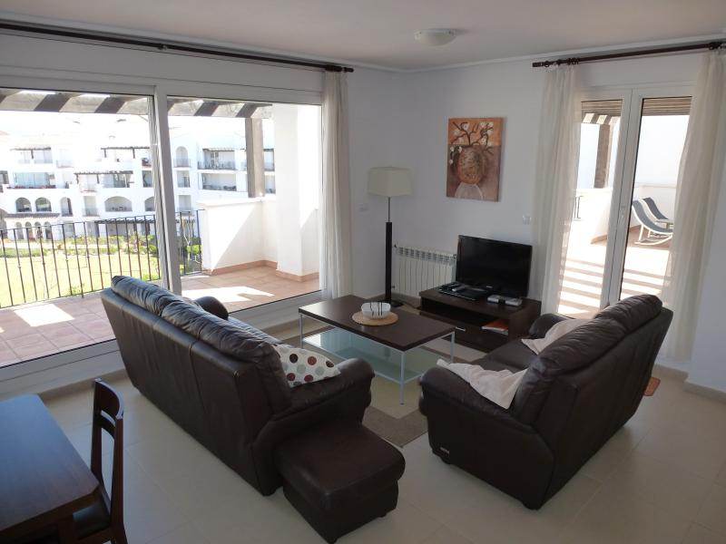 Lounge seating area with UK, Spanish and EuropeanTV channels, patio doors to the balcony and the ter