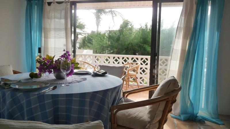 The dining area opens onto the balcony with glimpses of the sea through trees