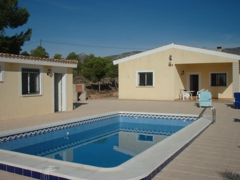 View of the main villa, pool, patio and pool house with shower and toilet