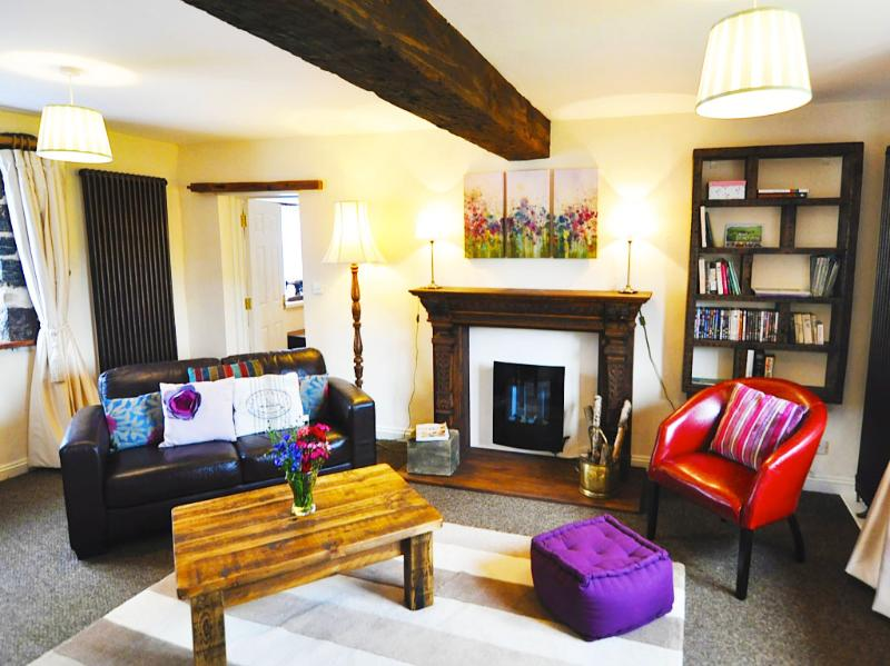 This exquisite cottage offers a living area with exposed beams and a stunning ornate mantelpiece...
