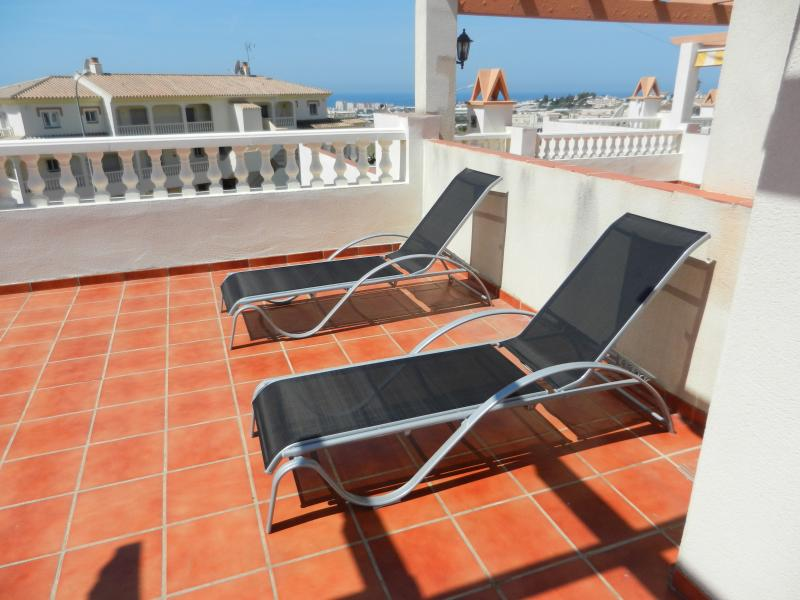 Sun loungers on roof terrace.