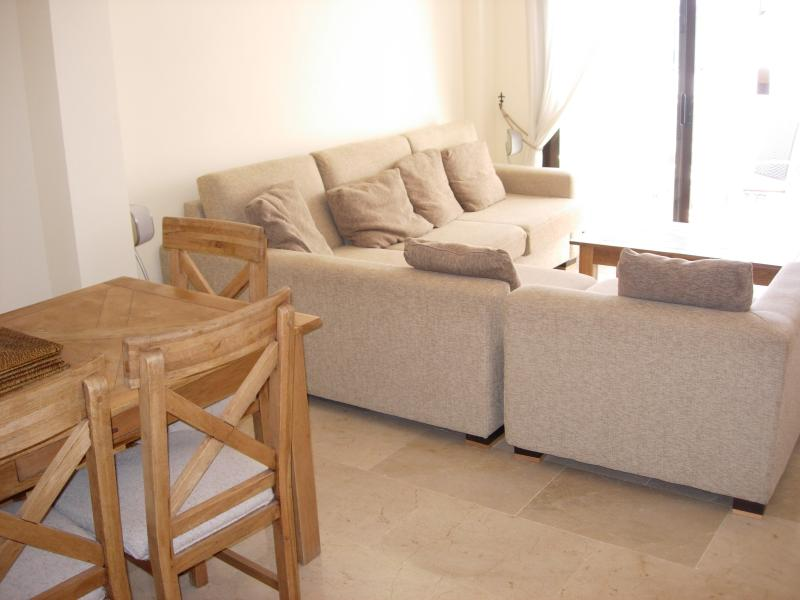 Large lounge/dining room with terrace overlooking the swimming pool, beach and sea.