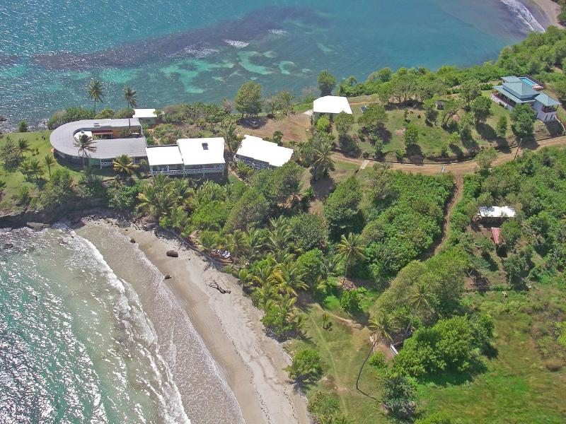 Two Bays Villa + infinity pool on right with sea and bay views & Cabier Lodge with bar & res