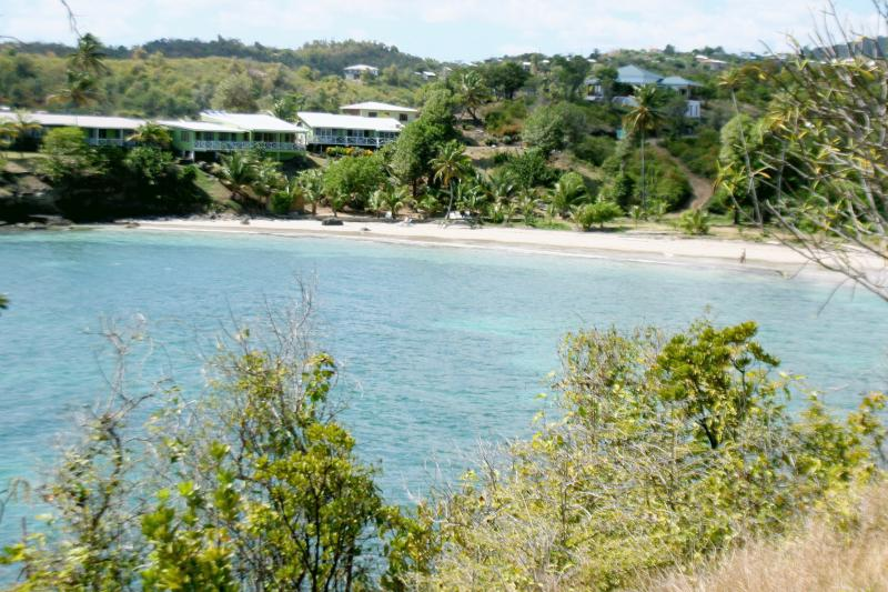 Two Bays Studios (blue roof) - above beautiful, natural, Cabier beach - protected by its reef.