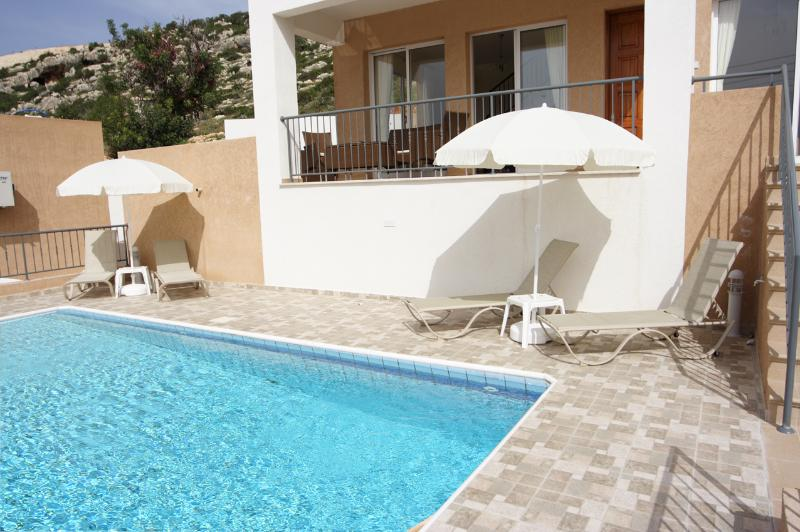 Large pool with sunbeds and sun parasols