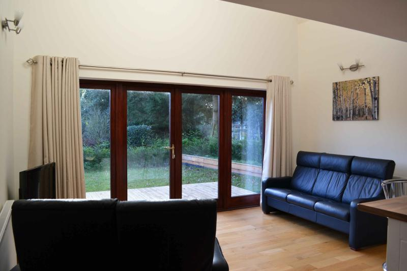 Open plan seating area with double doors to garden