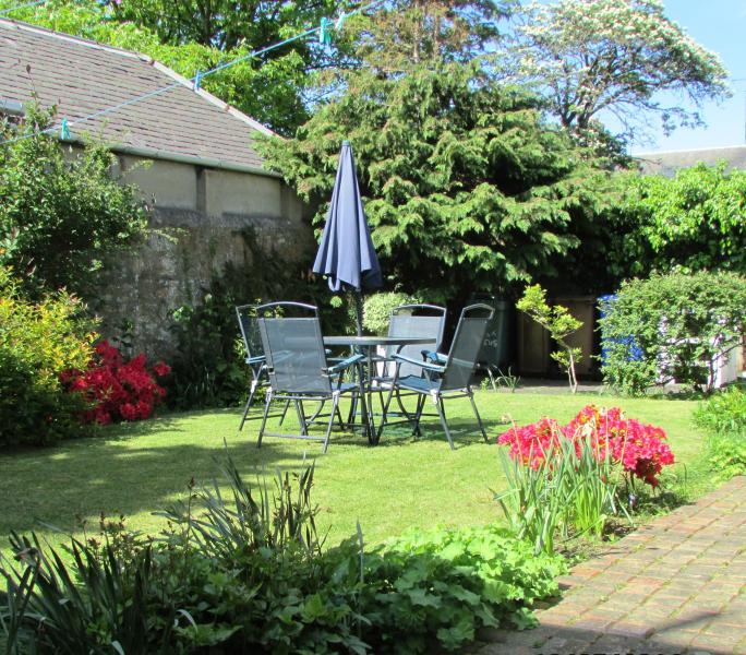 Jardin entièrement clos avec barbecue et mobilier d'extérieur.