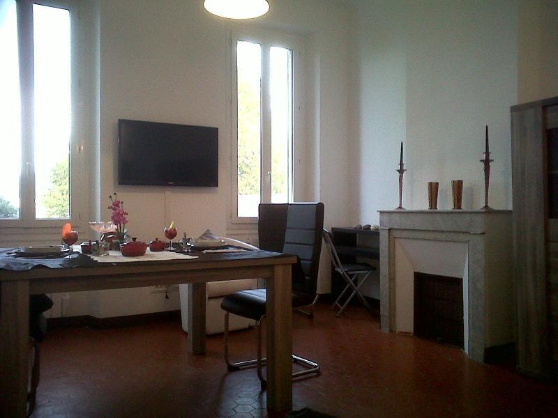 Salle de séjour vue du canapé avec table pour 8 personnes, TV et coin bureau