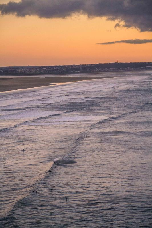 Surfing Saunton beach at sunset