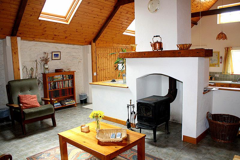 Horseshoe Cottage living has an attractive beamed ceiling and feature chimney and wood burning stove