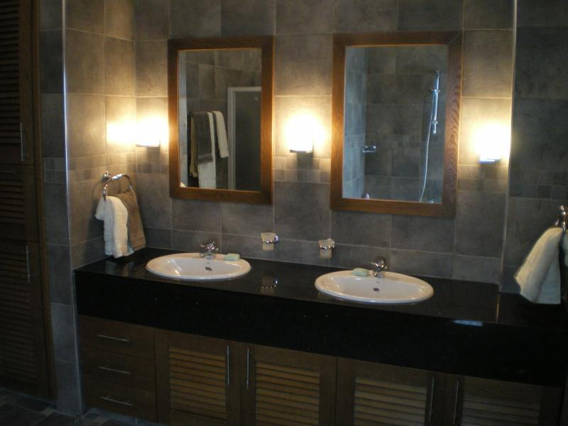 His and her amenities in large ensuite bathroom with semi-oval bath and spacious walk-in shower