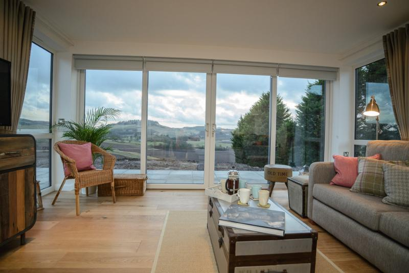 Patio living room windows overlook panoramic views of rolling countryside.