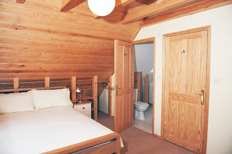 Dormitorio principal con baño en suite. Abrir el pino inclinado revestido del techo,