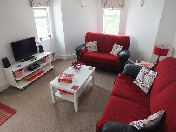 Showing the spacious living area with two double sofas one being the double sofa bed