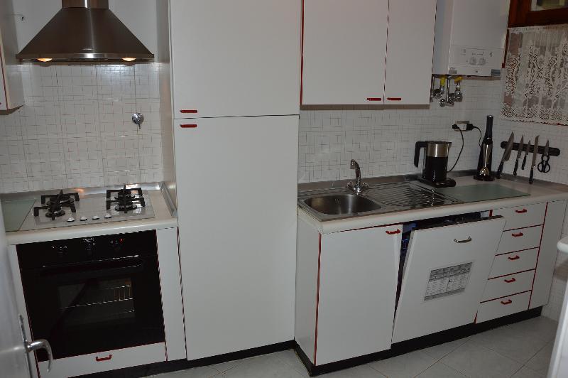 Cuisine avec cuisinière, lave-vaiselle sur la droite, réfrigérateur au milieu.