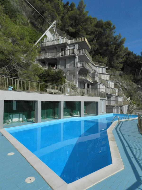 Vue sur les bains de mer avec piscine, une terrasse au-dessus de lui et les cabines