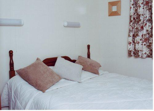 Double bedroom, comprises bed, wardrobe and set of drawers