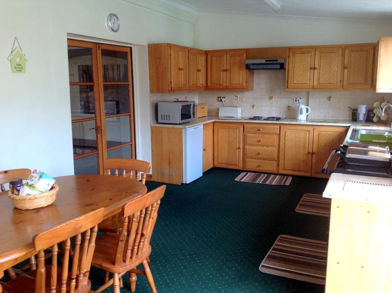 Large country kitchen with table to seat 6, traditional Rayburn oven and electric hob.