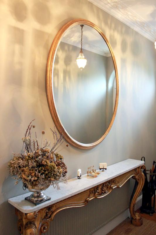 Entrance hallway detail with antique oval mirror and Regency console table
