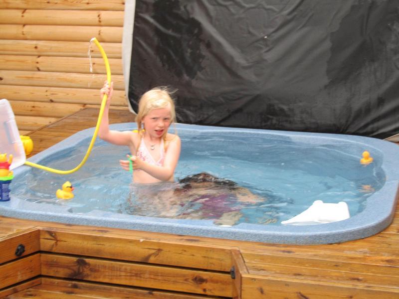 Bañera llena de agua de manantial caliente de la granja.  Niños encantan y pasan horas y horas allí