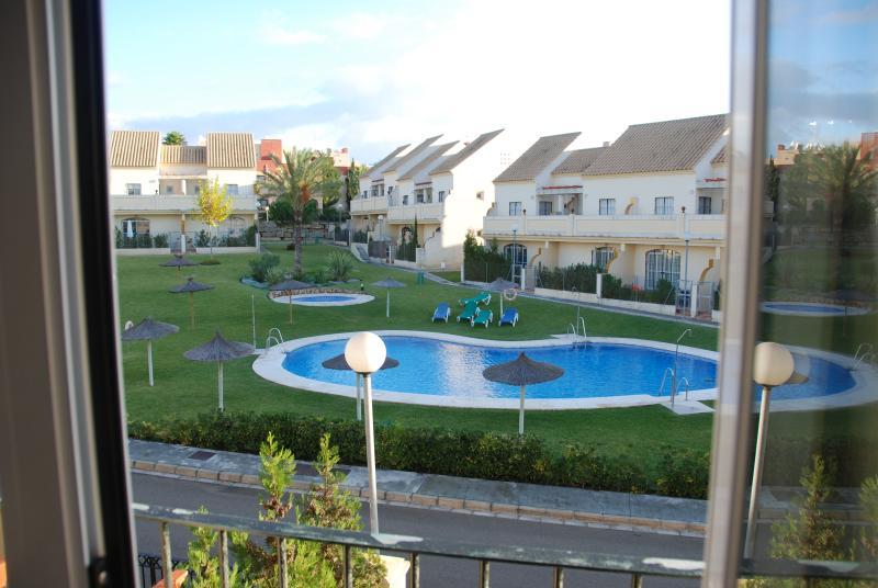 view from 2nd bedroom balcony, overlooking pool & gardens