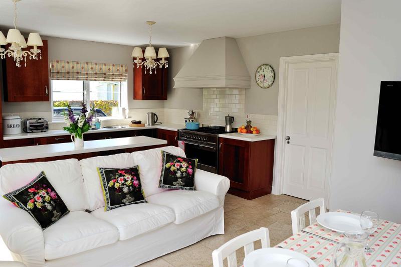 Grote keuken met alle moderne gemakken en grote comfortabele sofa om te ontspannen op.