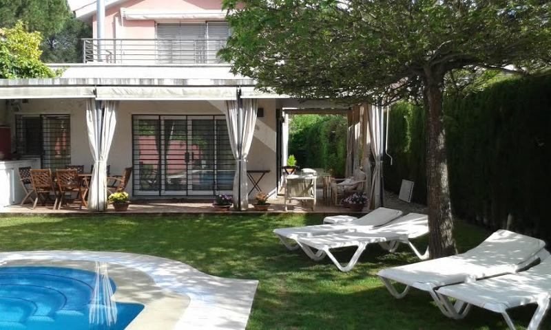 Vista jardín con piscina y porche