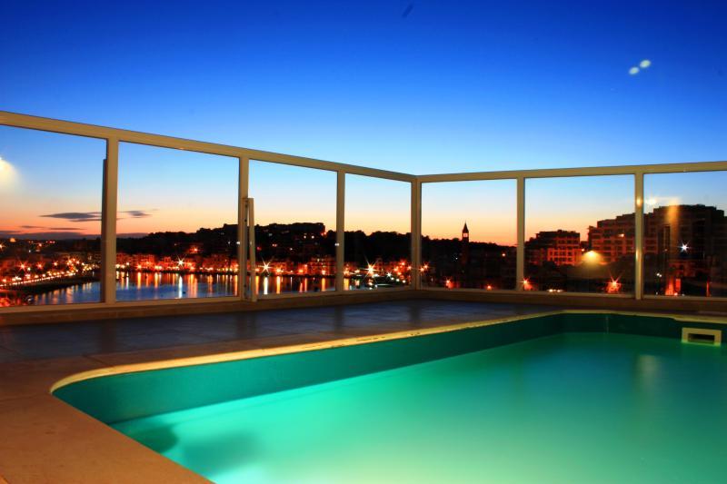 Piscina del ático con vistas al mar, en la noche
