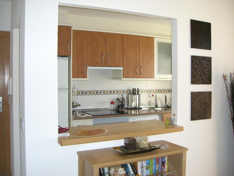 La escotilla de servicio y la barra de desayuno conectan la cocina con el comedor.