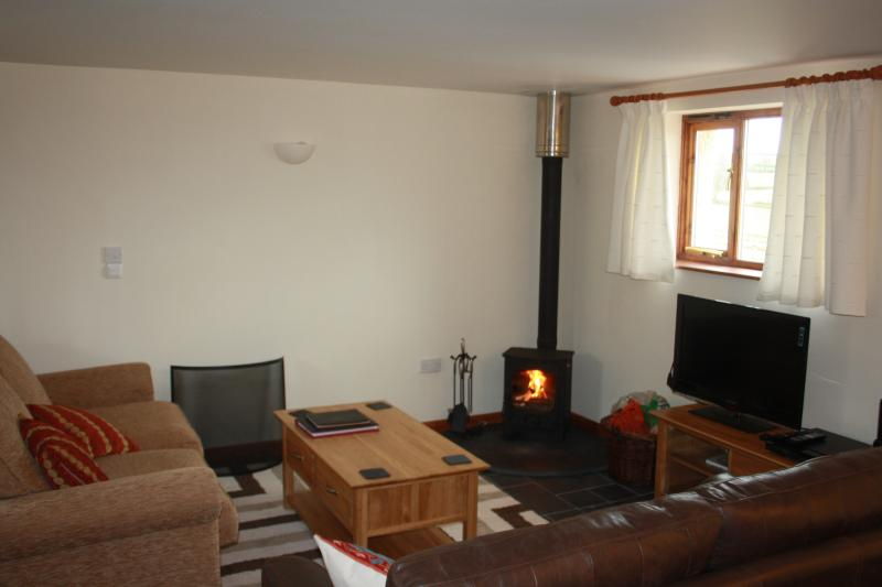 Lounge, furnished in oak and leather, underfloor heating, log fire