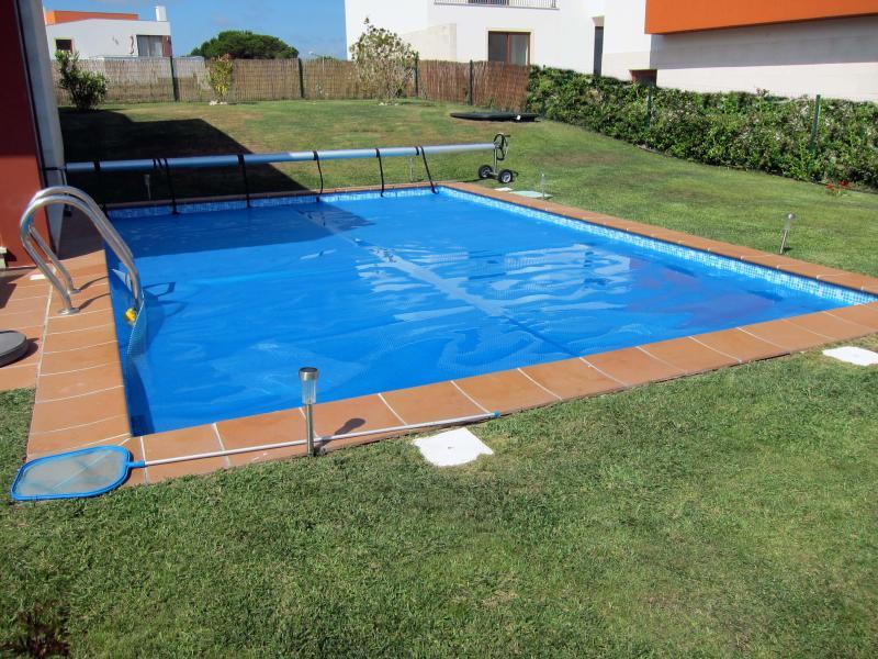 Zona de piscina con tumbonas y mesa de comedor exterior.