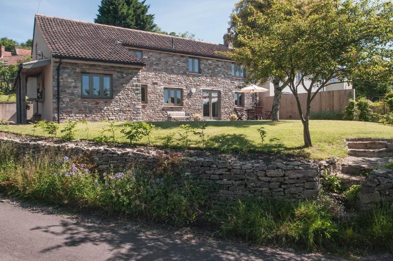 Contemporáneo cabaña de piedra con jardín soleado en entorno tranquilo pueblo.