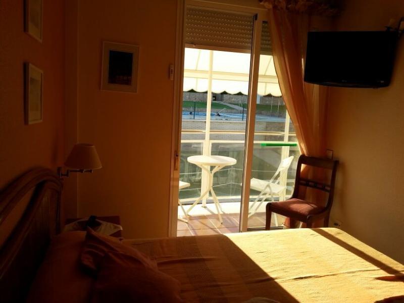 dormitorio principal con TV y vistas a la urbanización y a las montañas