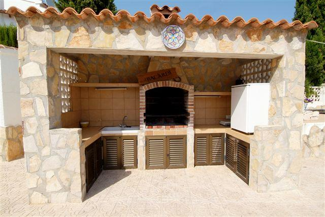 BBQ and outside kitchen area with a sink and a fridge