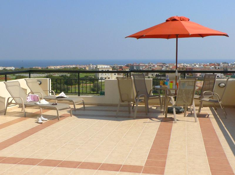 Large, sunny, private veranda with large table, chairs and sun loungers