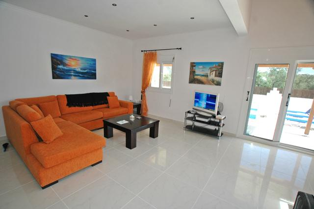 The spacious living area is comfortable and brightly furnished.