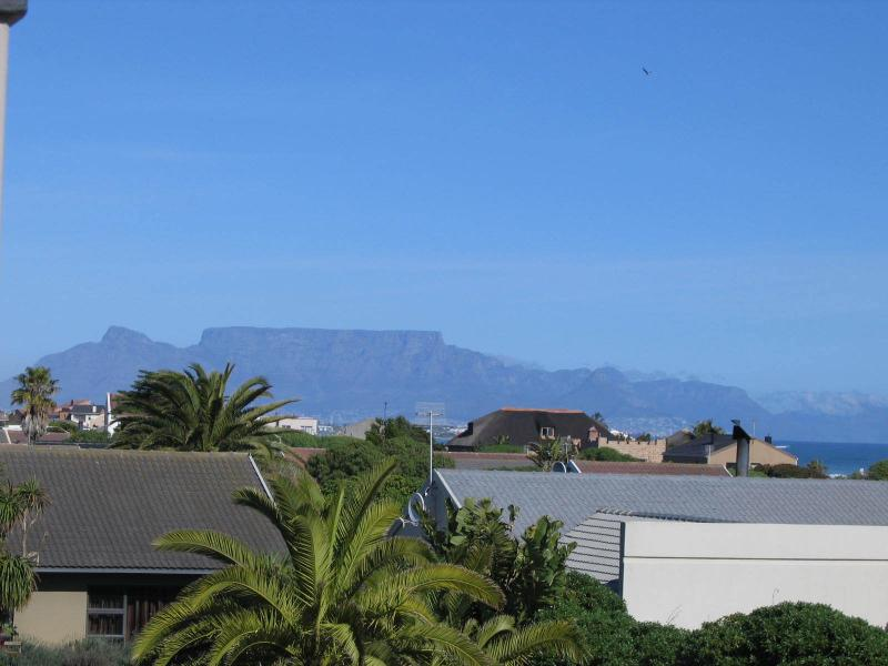 main bedroom and balcony view of sea and Table Mountain. 2 minutes walk to beach.