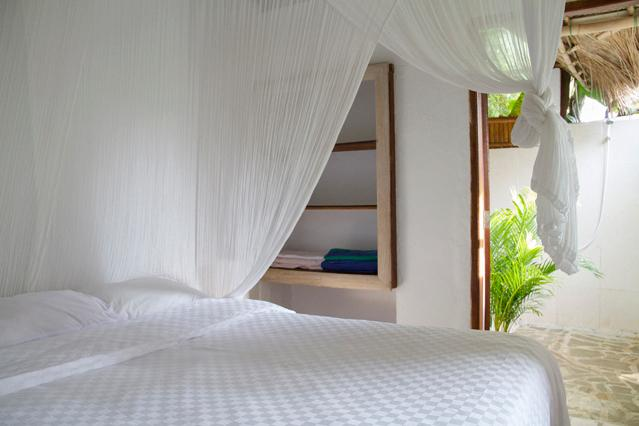 Surf bungalow's bedroom with mosquito net and AC and adjacent bathroom.