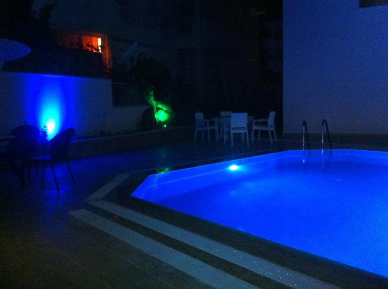 Romantic atmosphere at nights created by night lightening around garden and swimming pool