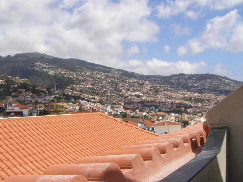 View from your bedroom balcony over the rooftops and out over Funchal and towards the mountains.