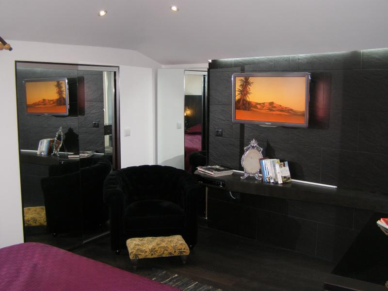 Wall mounted cable TV with 120 channels, plus easy chair and mirrored wardrobe in bedroom