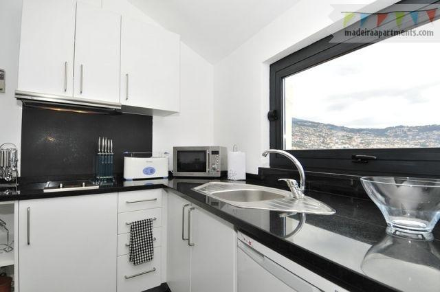 Your kitchen window has views over the city & out to sea, easy clean black granite worktops