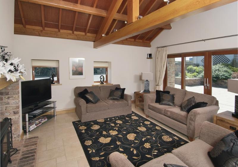 Spacious lounge with log fire, Wi-Fi, 42' TV/DVD player, underfloor heating, and views of the garden
